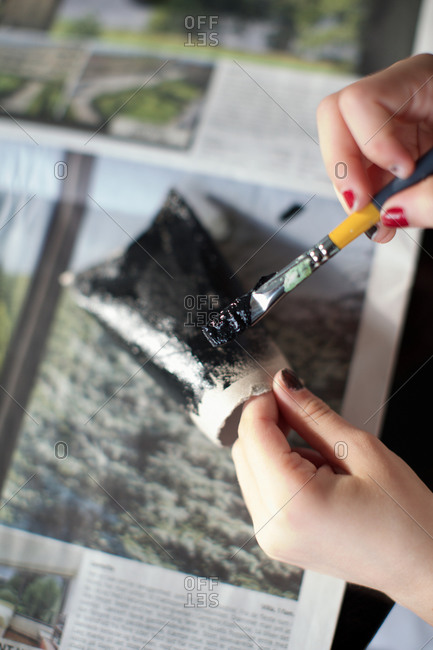 Girl painting homemade bat with a paintbrush