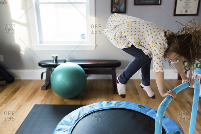 Girl jumping on a trampoline while holding onto a rail