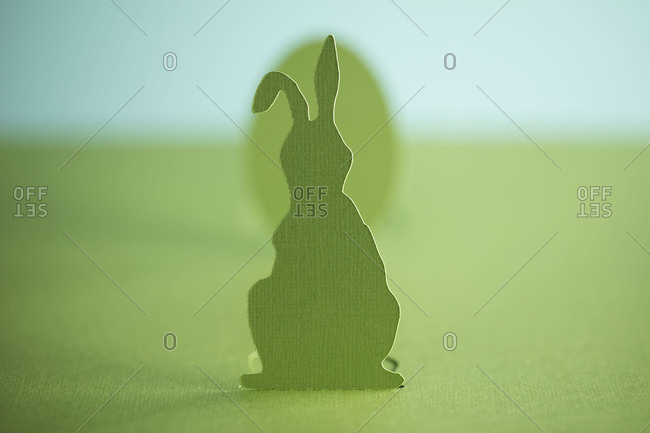 Close-up of a cutout of a green Easter bunny in front of an Easter egg