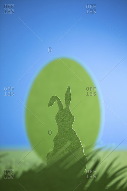 A cutout of an Easter bunny in a meadow in front of an Easter egg and a blue sky
