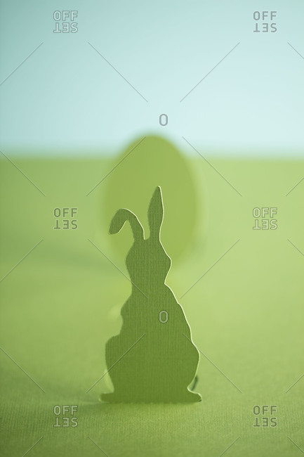 A cutout of a green Easter bunny in front of an Easter egg