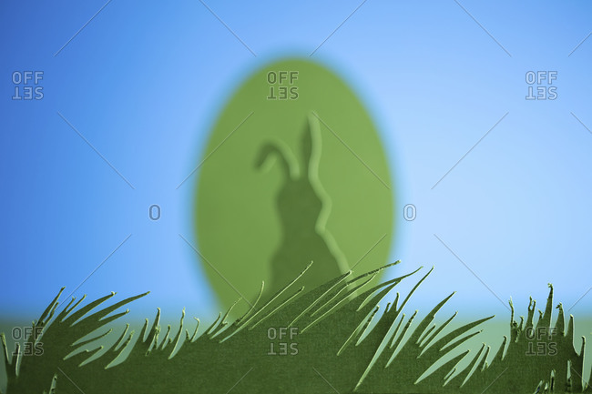 A cutout of a grassy meadow with an Easter bunny, Easter egg, and blue sky