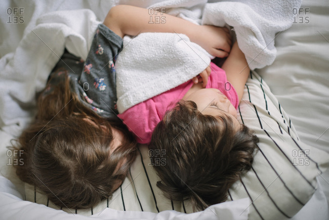 Two sisters cuddling in bed