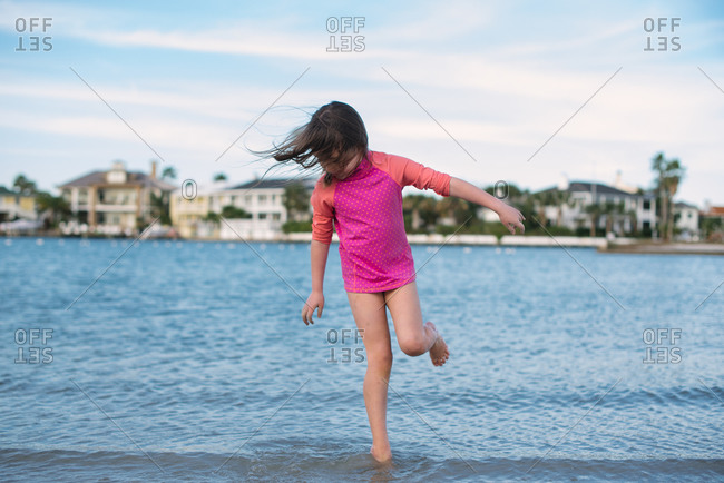 Girl balancing in ocean surf