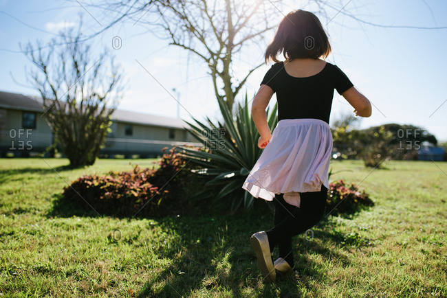 Girl in tutu in a yard