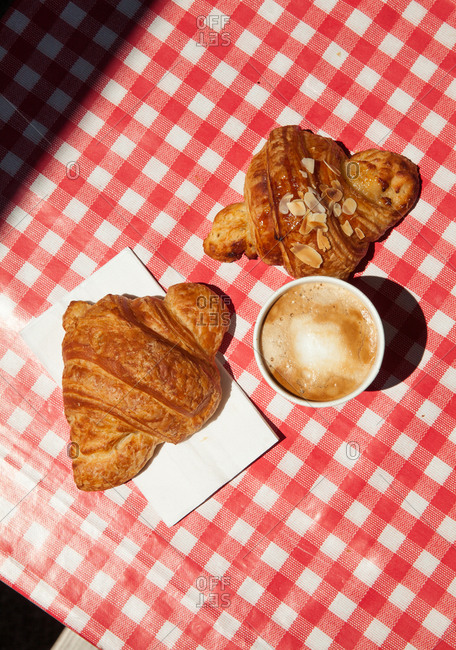 Croissant and coffee on a red-checkered tablecloth