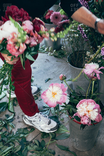 Woman picking flowers from metal buckets at a florist shop