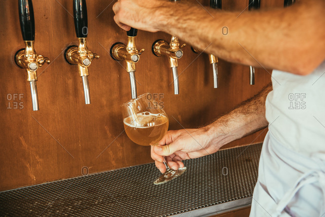 Server pouring beer into a glass from a tap