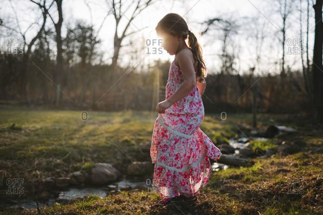 Girl by sunlit stream