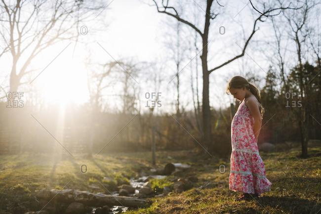 Girl by sun dappled stream