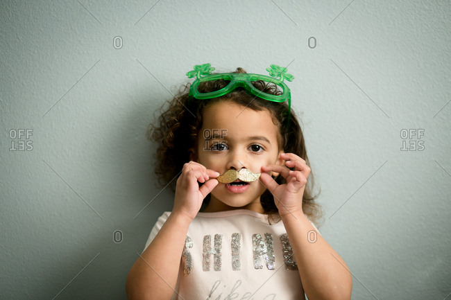 Biracial young girl wearing shamrock glasses and a golden mustache