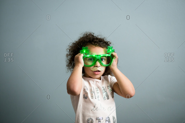 Little girl dressed up for St. Patrick's Day with light up glasses and mustache