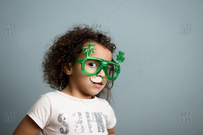 Young girl posing in shamrock glasses and gold glitter mustache