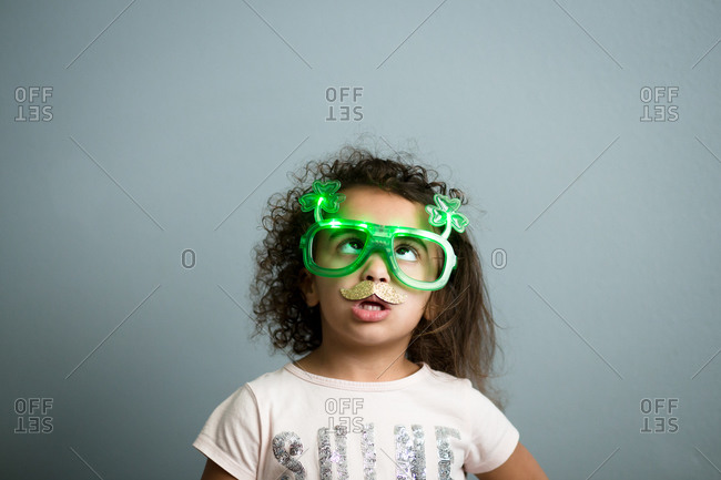Young girl in glitter mustache looking up at her lighted shamrock glasses