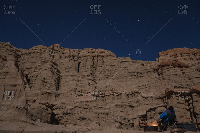 Person gazing at stars while camping below cliffs in California desert