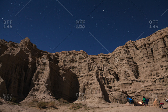 Two people around campfire at desert cliffs below a starry night sky