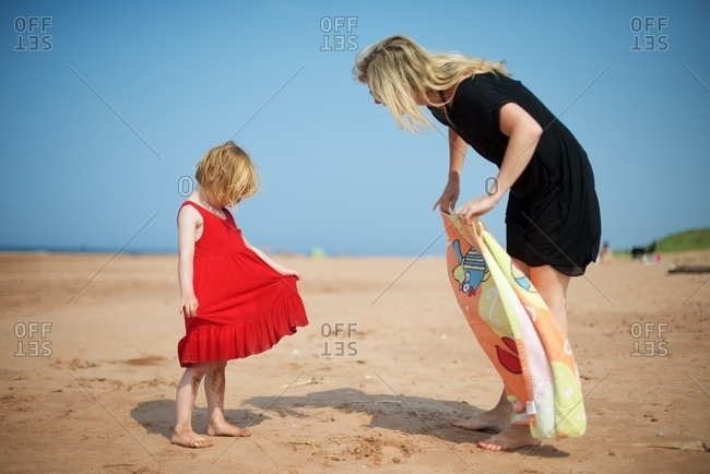 Little girl looks at and holds her red dress while her mother unfolds a beach towel