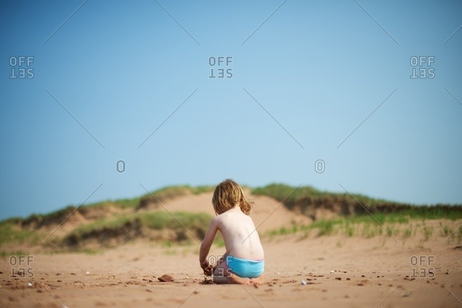 Little girl in her panties playing in the sand at the beach