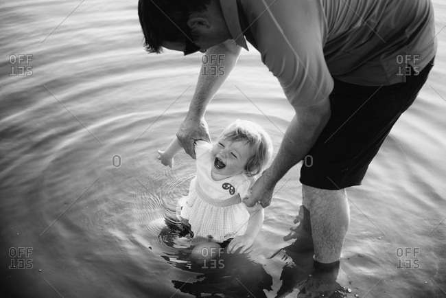 Toddler laughing while her father dips her legs in the water