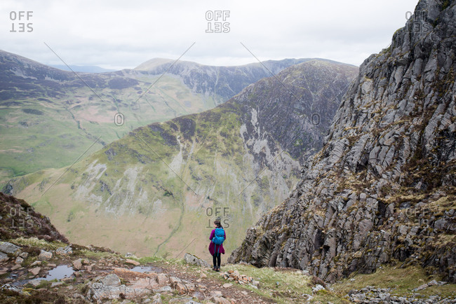 A hiker in the Lake District in England standing near the top of Haystacks above Butteremere