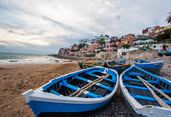 Taghazout, Morocco - April 19, 2014: Fishing boats and sandy beaches with calm waves on a sunny day