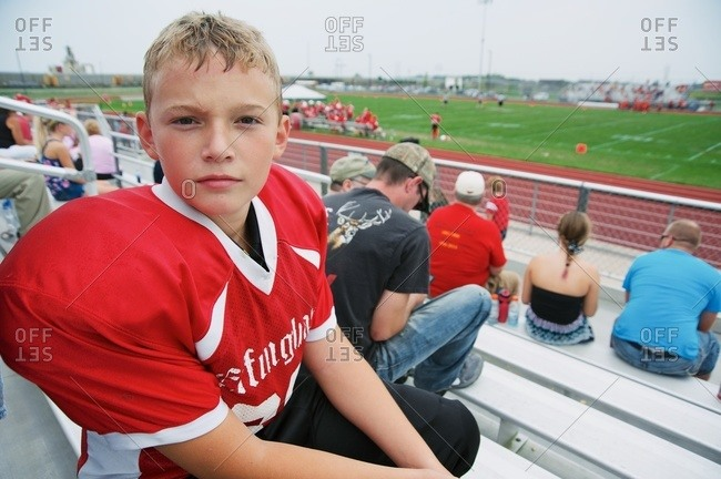Boy in football jersey at game