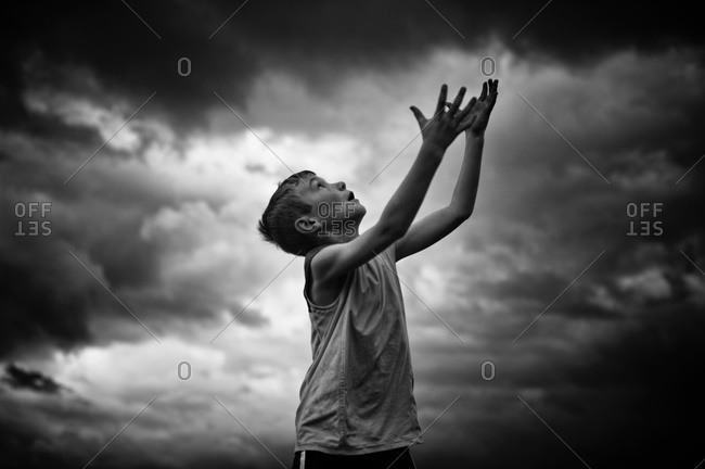 Boy throwing ball against clouds