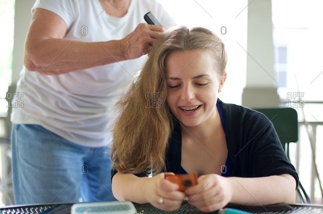 Woman doing teen girl's hair