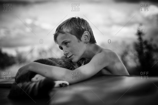 Boy snuggling a cat outside