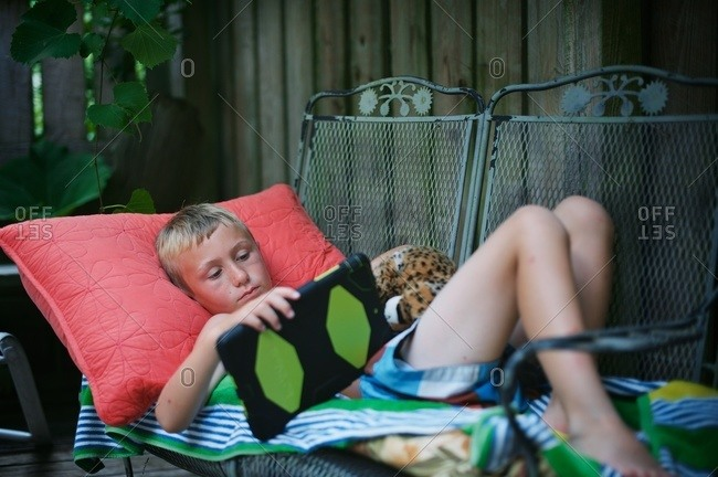Boy on patio furniture with tablet