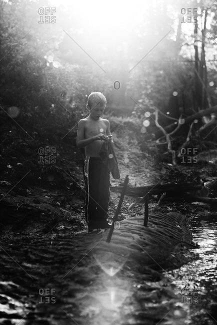 Boy near sun dappled stream