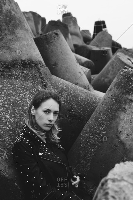 Young woman leaning against tetrapods