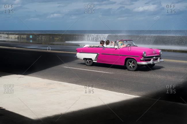 Cuba - March 7, 2016: Vintage hot pink convertible driving across bridge