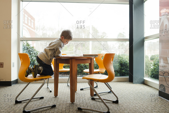 Boy reading at a library table