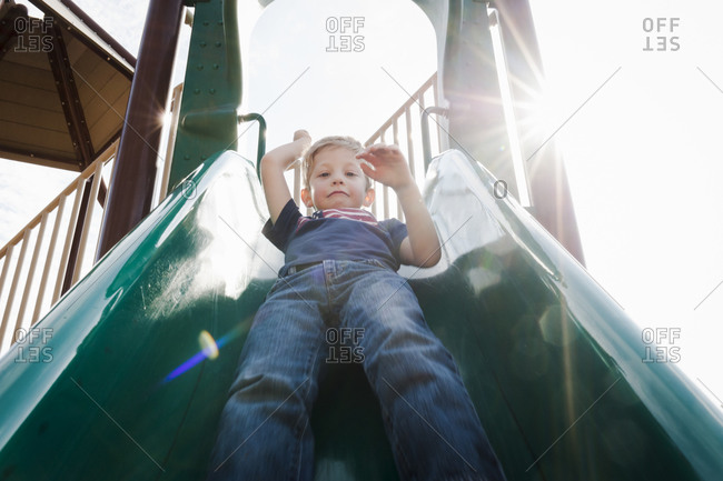 Boy doing down playground slide