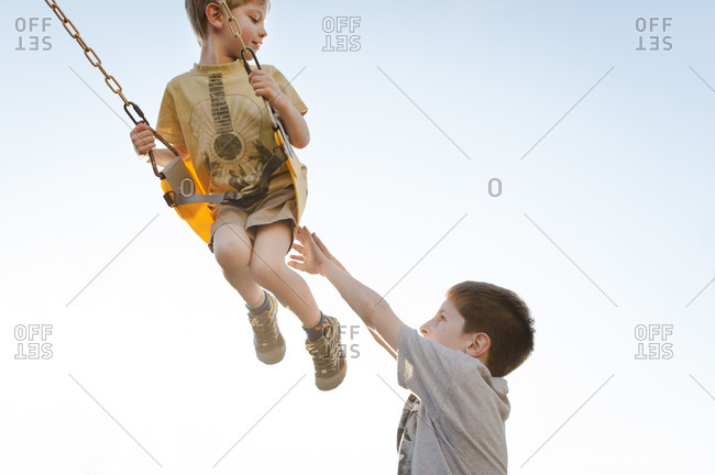 Boy pushing another on swing