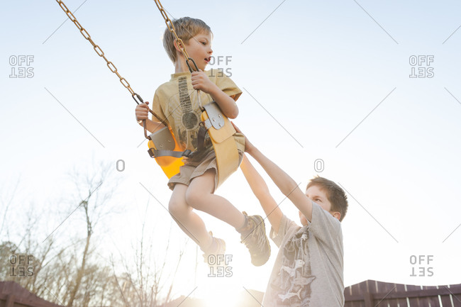 Boy pushing another on a swing