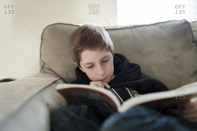 Boy reading his book on couch