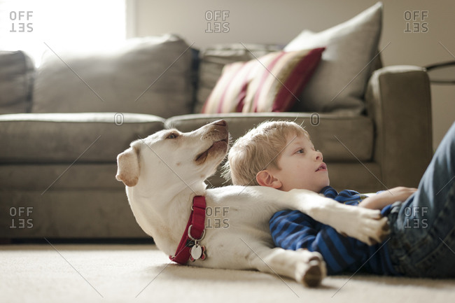 Boy lying on dog on floor