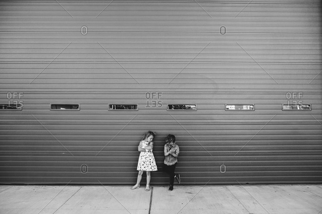 Two children standing in front of a garage door with their arms crossed