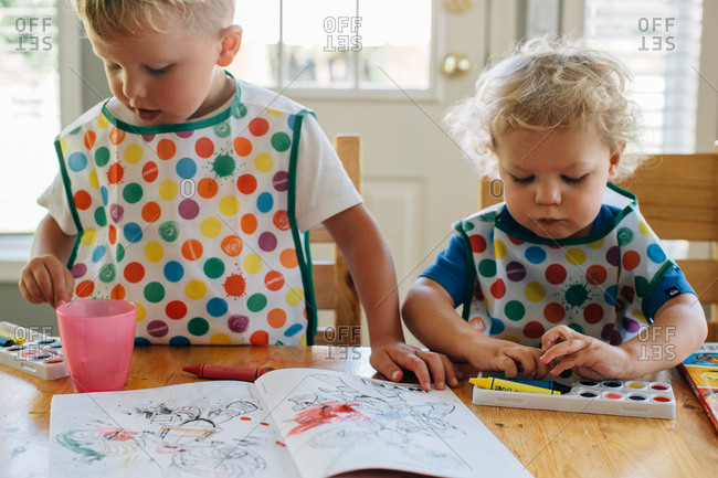 Children wearing colorful smocks and painting