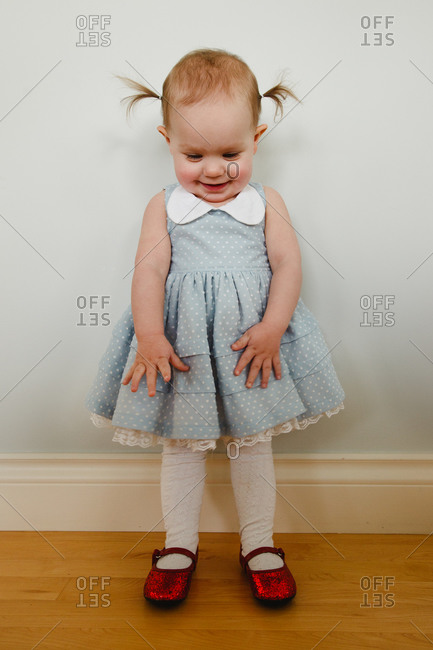 Portrait of a girl wearing a blue dress and red sparkly shoes