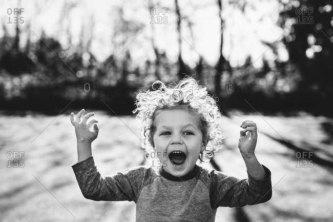 Child outside yelling with arms raised