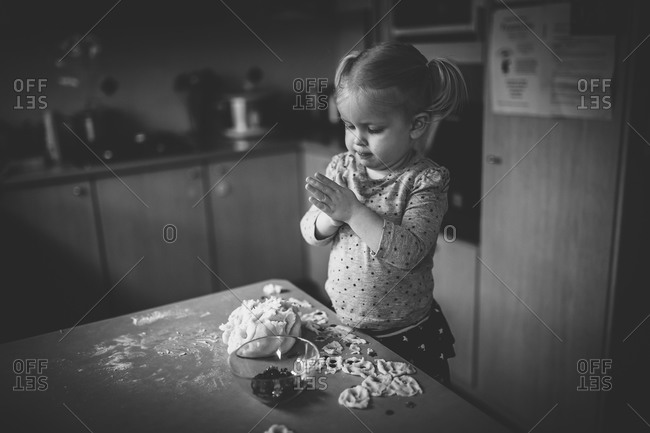 Little girl playing with a dough and sequins