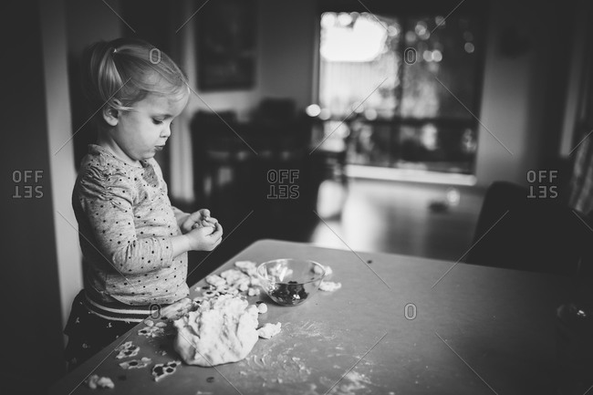 Little girl making a craft with dough and sequins