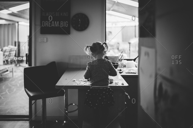 Little girl making a craft in the kitchen