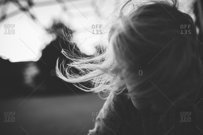 Little girl looking down with hair blowing in the wind