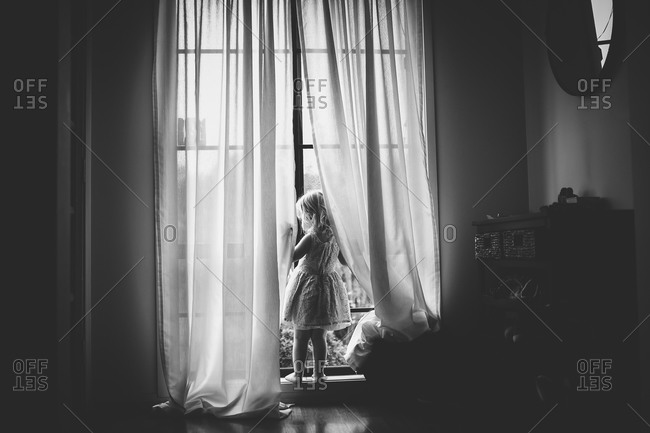 Little girl looking out a window in a white dress