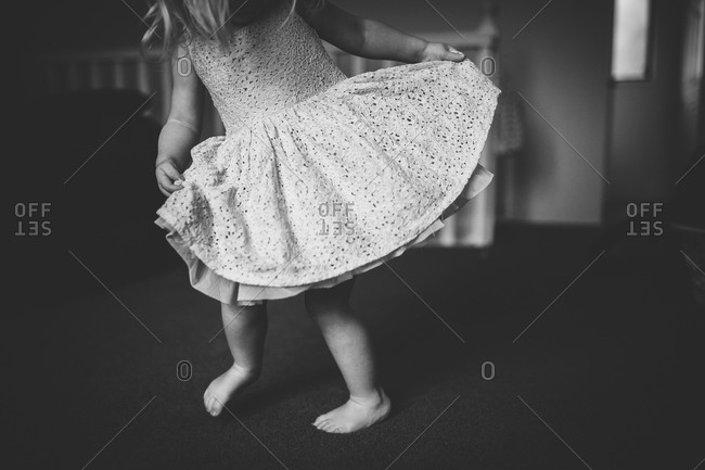 Little girl dancing around in a white dress
