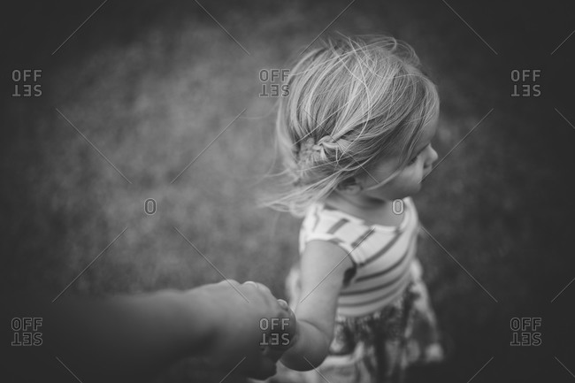 High angle view of little girl holding parent's hand